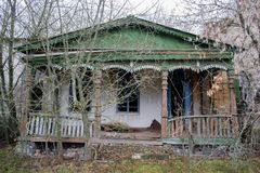 Det gamla, eftersatta lordly huset och farstubron bland träden Textur av gammalt sprucket trä målad gräsplan royaltyfria bilder