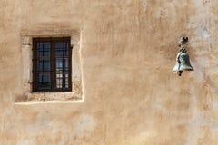 Det gamla fängelseväggfönstret med järnstänger och varningsklocka fotografering för bildbyråer