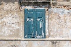 Det gamla fönstret i blått färgar på den smutsiga väggen Fotografering för Bildbyråer