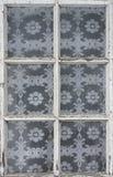 Det gamla fönstret i ett av byhusen, många fyrkanter utformar Fotografering för Bildbyråer