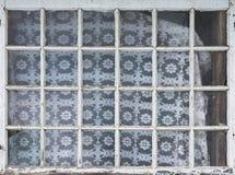 Det gamla fönstret i ett av byhusen, många fyrkanter utformar Arkivbild