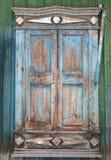Det gamla fönstret med den spruckna dekorativa ramen och stormen stänger med fönsterluckor clos Arkivfoton