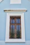 Det gamla fönstret, med ett metallgaller Arkivbild