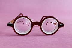Det gamla glasögon för modedesignanblickar på rosa violet skyler över brister bakgrund Tillbehör för mode för tappningstilmän för royaltyfria foton