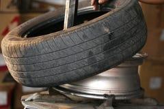 Det gamla gummihjulet byter ut Royaltyfri Foto
