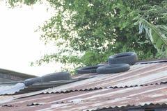 Det gamla gummihjulet förläggas på ett zinktak för att förhindra zink från blåst bort av stormen royaltyfria foton