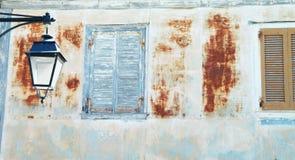 Det gamla huset med skadade väggar och blått stänger med fönsterluckor med lyktan Fotografering för Bildbyråer