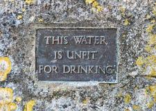 Det gamla i dålig kondition dricksvattentecknet ställde in i sten royaltyfria foton