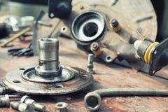 Det gamla oljde hjulnavet ligger på en trätabell Royaltyfri Foto