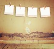Det gamla polaroidfotoet inramar att hänga på ett rep över texturerad grungevägg- och golvmodell Royaltyfria Bilder