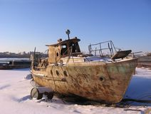 Det gamla rostiga fartyget som förtöjdes till kusten i vintern, fryste på floden royaltyfri bild