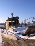 Det gamla rostiga fartyget som förtöjdes till kusten i vintern, fryste på floden royaltyfria foton