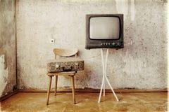Det gamla rummet med ett retro TV:N, en stol och en resväska Royaltyfri Bild