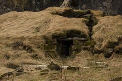Det gamla stenhuset förstörde den forntida vikingen som var bevuxen med gult torrt gräs royaltyfria bilder