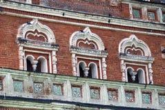 Det gamla tornet av röda tegelstenar dekorerade vid keramiska tegelplattor Fotografering för Bildbyråer