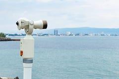 Det gamla touristic teleskopet med den suddiga staden och havet landskap bakgrund Royaltyfri Bild