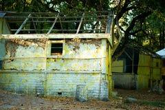 Det gamla träförstörda huset är gult Lantlig övergiven koja övergivet hus Royaltyfri Bild