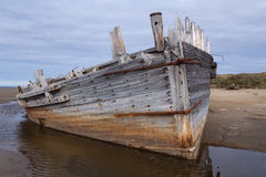 Det gamla träskeppet strandade på en sandig strand Arkivfoton