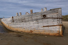Det gamla träskeppet strandade på en sandig strand Arkivbild
