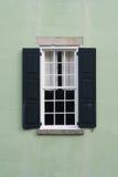 Det gammala koloniala fönstret med stänger med fönsterluckor Arkivbilder
