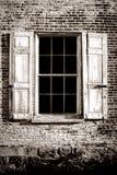 Det gammalt fönstret och trä stänger med fönsterluckor på den forntida tegelstenväggen Royaltyfri Fotografi