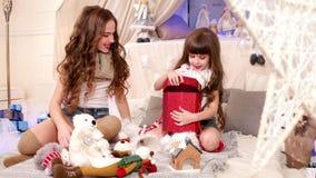 Det glade ögonblicket av att ge gåvor, ger den äldre systern en mest ung julgåva, familjen som firar julaftonen som är lycklig stock video