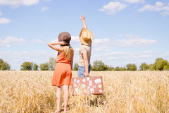 Det glade barnet kopplar ihop att ha gyckel i vetefält Upphetsad man och kvinna som pekar på utomhus- blå himmel Arkivfoton