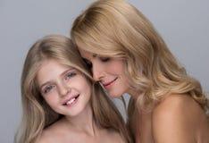 Det glade barnet ler, medan stå med hennes mamma royaltyfri bild