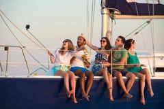 Det glade företaget firar födelsedag på en yacht Arkivbild