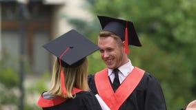 Det glade paret i akademiker klär att krama och att skratta, lycklig framtid, utbildning stock video