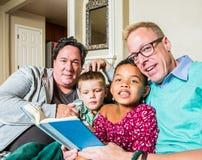 Det glade paret läser till barn Fotografering för Bildbyråer