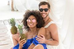 Det glade ungdomliga paret som tycker om sommar, dricker på semesterort Arkivfoton