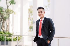 Det gladlynta asiatiska anseendet för affärsman parkerar in royaltyfri foto
