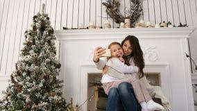 Det gladlynta barnet fostrar och hennes selfies för xmas för dotterdanande komiska och visningtungor arkivbild