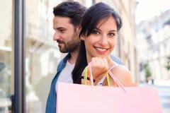 Det gladlynta barnet kopplar ihop att shoppa tillsammans i staden som har gyckel arkivfoto