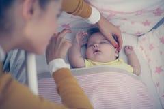 Det gladlynta barnet som modern sover henne, behandla som ett barn Arkivfoton