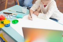 Det gladlynta kvinnliga barnet målar med farfadern royaltyfria foton