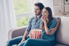 Det gladlynta paret håller ögonen på hemmastadd komedi inomhus och att äta popco royaltyfria foton