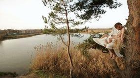 Det gladlynta paret sitter på trädet nära floden Den attraktiva kvinnan lägger på manbenen stock video