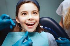 Det gladlynta positiva barnet sitter i tand- stol Händer i latexhandskar som floss framtänder Asisstant stan för kvinna bredvid royaltyfria bilder