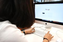 Det Google sökandebegreppet, användare skriver nyckelord i Google sökandestång på datorwebbläsaren arkivfoto