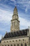 Det gotiska stadshuset och dess klockstapeltorn i den franska stadsarrasen på en blå himmel med vitmoln bakgrund, världsarv vid U Fotografering för Bildbyråer