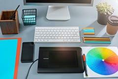 Det gråa skrivbordet med bärbara datorn, notepaden med det tomma arket, krukan av blomman, nålen och minnestavlan för att retusch Royaltyfria Foton