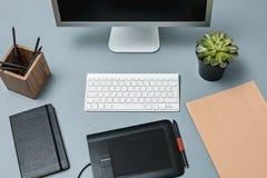 Det gråa skrivbordet med bärbara datorn, notepaden med det tomma arket, krukan av blomman, nålen och minnestavlan för att retusch Royaltyfri Foto