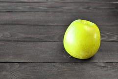 Det gröna äpplet ligger på en trätabell arkivbild