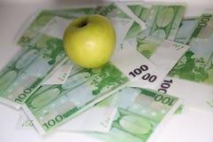 Det gröna äpplet ligger på valörer hundra euro Royaltyfri Fotografi