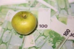 Det gröna äpplet ligger på valörer hundra euro Royaltyfria Bilder