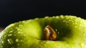 Det gröna äpplet med vattendroppar roterar på svart bakgrund arkivfilmer
