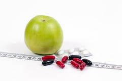 Det gröna äpplet och vitaminer som är healty bantar Arkivbild