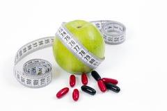 Det gröna äpplet och vitaminer som är healty bantar Royaltyfri Foto